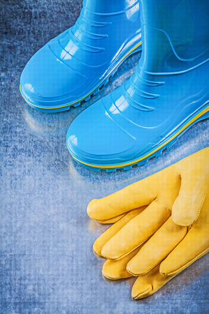 gum boots: Waterproof rubber boots leather safety gloves on metallic background gardening concept.