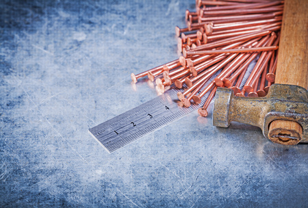 construction nails: Vintage claw hammer copper construction nails metal ruler on metallic background. Stock Photo