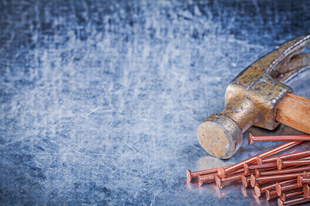 claw hammer: Claw hammer copper construction nails on metallic background. Stock Photo