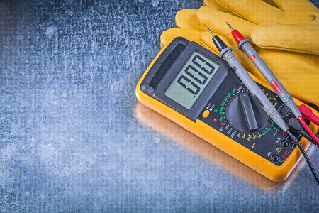 test probe: Digital electrical tester safety gloves on metallic background electricity concept.
