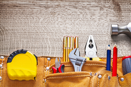 tool belt: Leather tool belt with construction equipment on wooden board. Stock Photo