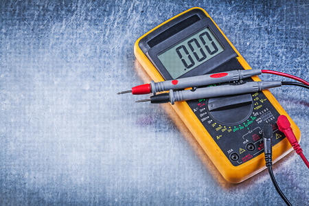 dielectric: Digital electrical tester wires current probe on metallic background.