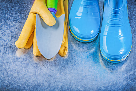 gumboots: Safety gumboots protective gloves hand trowel on metallic background gardening concept.