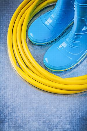 gum boots: Safety rubber boots garden hose on metallic background gardening concept.