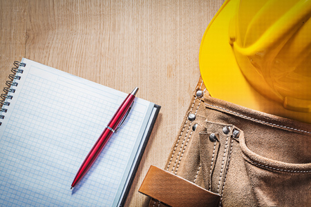 toolbelt: Leather toolbelt safety hard hat checked notepad pen on wood board. Stock Photo