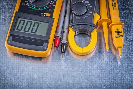 test probe: Composition of digital clamp meter electrical tester multimeter on metallic background electricity concept. Stock Photo