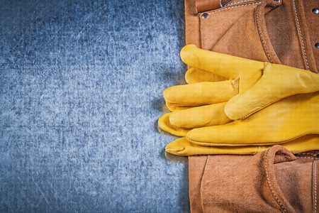toolbelt: Pair of protective gloves toolbelt on metallic background construction concept. Stock Photo