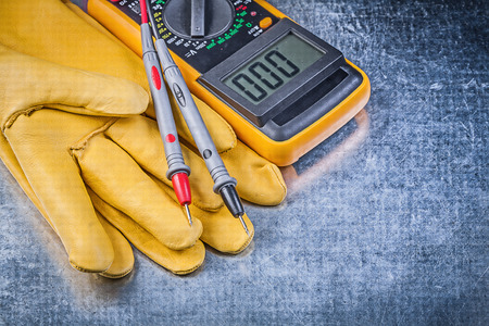 dielectric: Digital electrical tester safety gloves on metallic background. Stock Photo