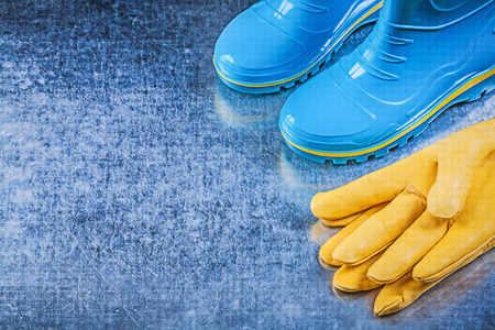 gumboots: Waterproof gumboots leather safety gloves on metallic background gardening concept.