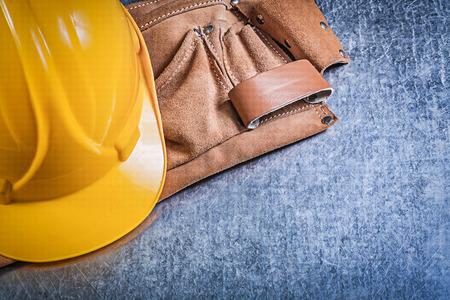 tool belt: Leather tool belt protective building helmet on metallic background construction concept.