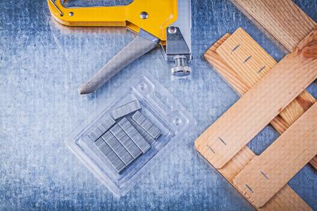 staple gun: Set of stapler gun chrome staples wooden building board on metallic background. Stock Photo