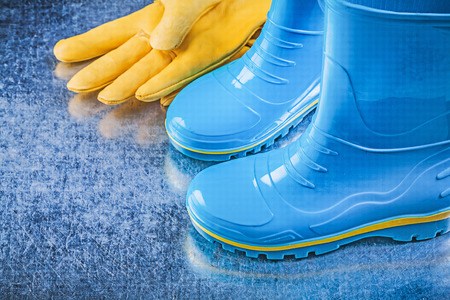 gum boots: Pair of waterproof rubber boots leather safety gloves on metallic background gardening concept.