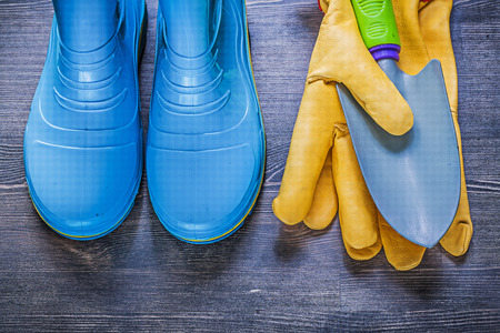 gumboots: Gardening protective gloves metal hand spade waterproof gumboots on wooden board agriculture concept. Stock Photo