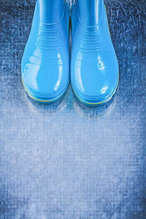 rubber boots: Pair of protective rubber boots on metallic background gardening concept.