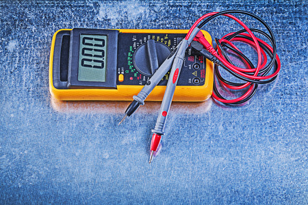 dielectric: Digital electrical tester test leads on metallic background.