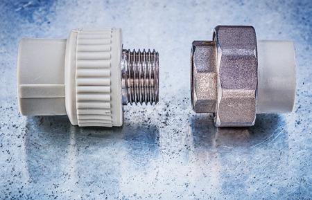 kunststoff rohr: Gewinderohrverbinder auf metallischen Hintergrund Bau-Konzept.
