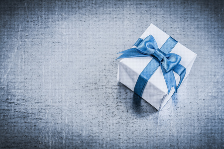 giftbox: Giftbox with tied bow on metallic background holidays concept.