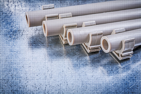 waterpipe: Pvc water-pipes pipe clamps on metallic background construction concept.