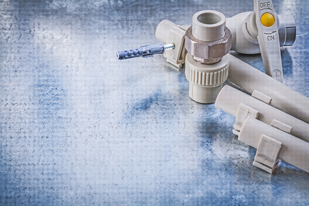 waterpipe: Plastic water pipe valve clamps connectors on metallic background construction concept.