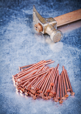 construction nails: Vintage claw hammer heap of copper construction nails on metallic background.