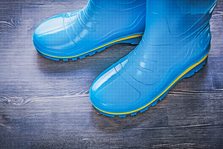 gumboots: Waterproof gardening gumboots on wood board agriculture concept. Stock Photo