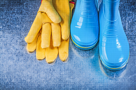 Protective rubber boots leather gloves on metallic background gardening concept.