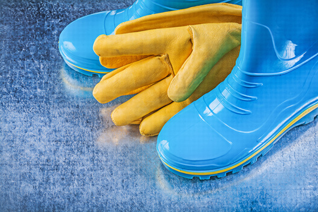 gum boots: Rubber boots leather gloves on metallic background gardening concept.