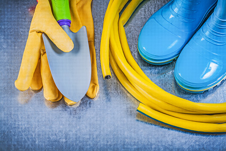 gum boots: Rubber boots garden hose protective gloves hand spade on metallic background gardening concept. Stock Photo