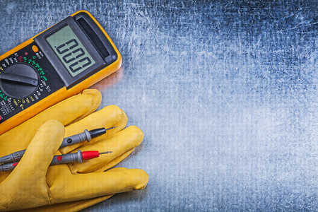 the tester: Digital electric tester safety gloves on metallic background electricity concept. Stock Photo