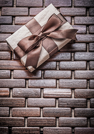 matting: Wrapped present with ribbon on wooden wicker matting holidays concept.