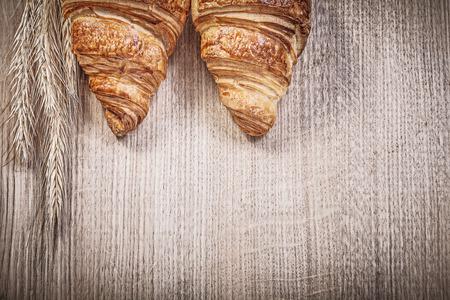 Ripe wheat rye ears newly-baked croissants on wooden board. Stock Photo