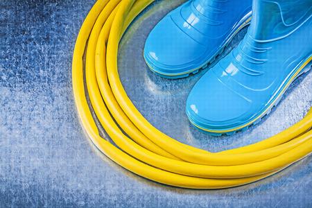 gum boots: Waterproof rubber boots hose on metallic background gardening concept.