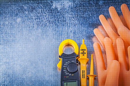 ammeter: Digital ammeter electrical tester dielectric rubber gloves on metallic background. Stock Photo