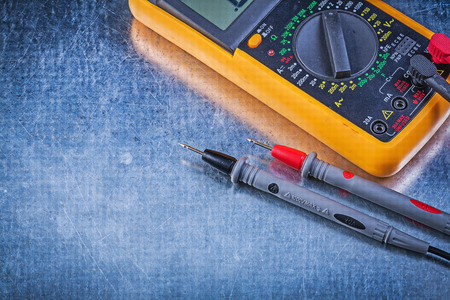 dielectric: Digital electrical tester on metallic surface close up view electricity concept.