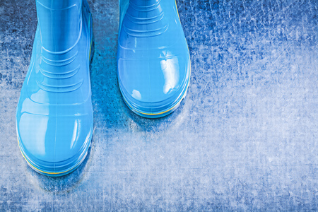 rubber boots: Waterproof rubber boots on metallic background.