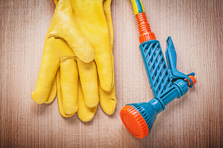 working gloves: Leather working gloves garden rubber hose nozzle on wooden board gardening concept.
