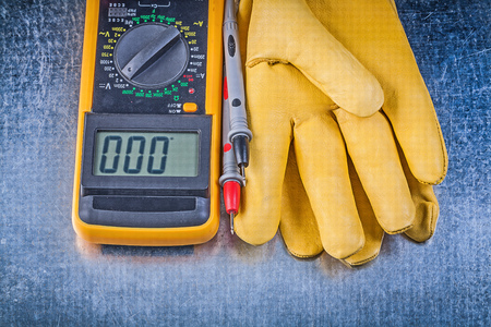 test probe: Digital electric tester test leads safety gloves on metallic background. Stock Photo