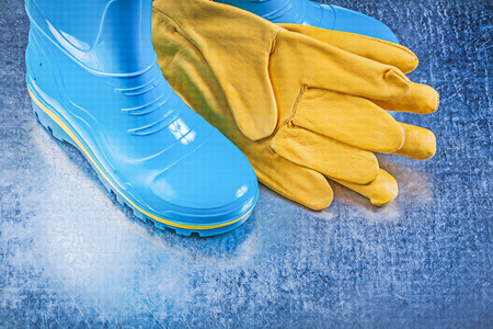 gum boots: Safety rubber boots leather gloves on metallic background gardening concept.