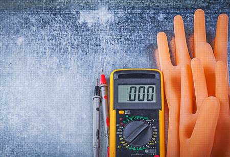 dielectric: Digital multimeter dielectric rubber gloves on metallic background electricity concept.