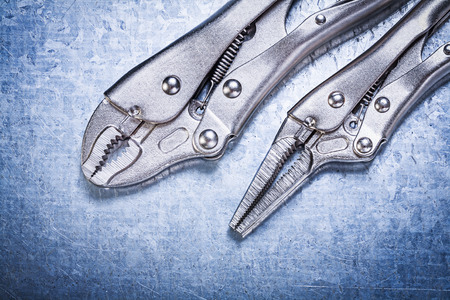 locking: Locking pliers with closed jaws on metallic background construction concept. Stock Photo
