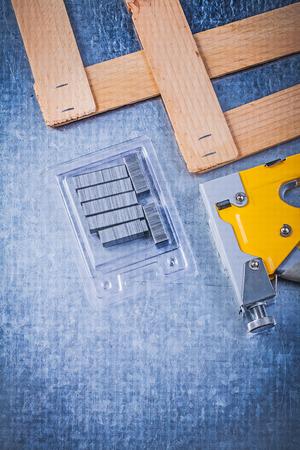 staple gun: Assortment of stapler gun metal staples wooden plank on metallic background construction concept. Stock Photo
