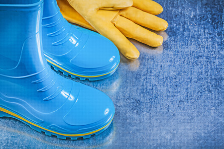 gum boots: Waterproof rubber boots leather protective gloves on metallic background gardening concept.