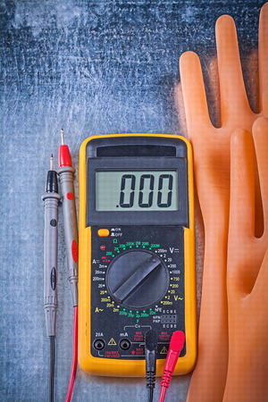 dielectric: Digital multimeter dielectric rubber gloves on metallic background vertical version electricity concept. Stock Photo