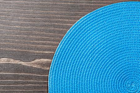 matting: Blue wicker table matting on wooden board.