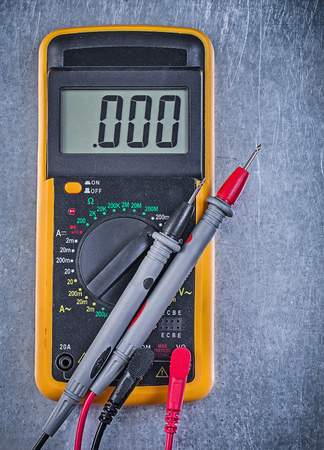 test probe: Digital electrical tester wires test leads on metallic background.