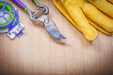 pruning shears: Yellow safety gloves pruning shears garden soft tie on wood board gardening concept.