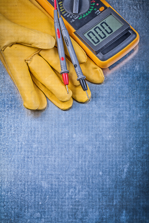 dielectric: Digital electrical tester protective gloves on metallic background.