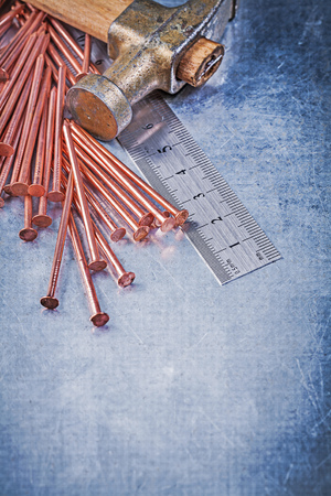 construction nails: Set of vintage claw hammer brass construction nails metal ruler on metallic background.
