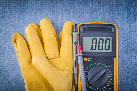 electric current: Digital electric tester current probe pair of safety gloves on metallic background.