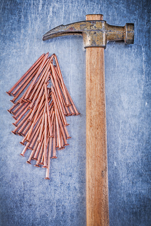 construction nails: Composition of vintage claw hammer copper construction nails on metallic background.